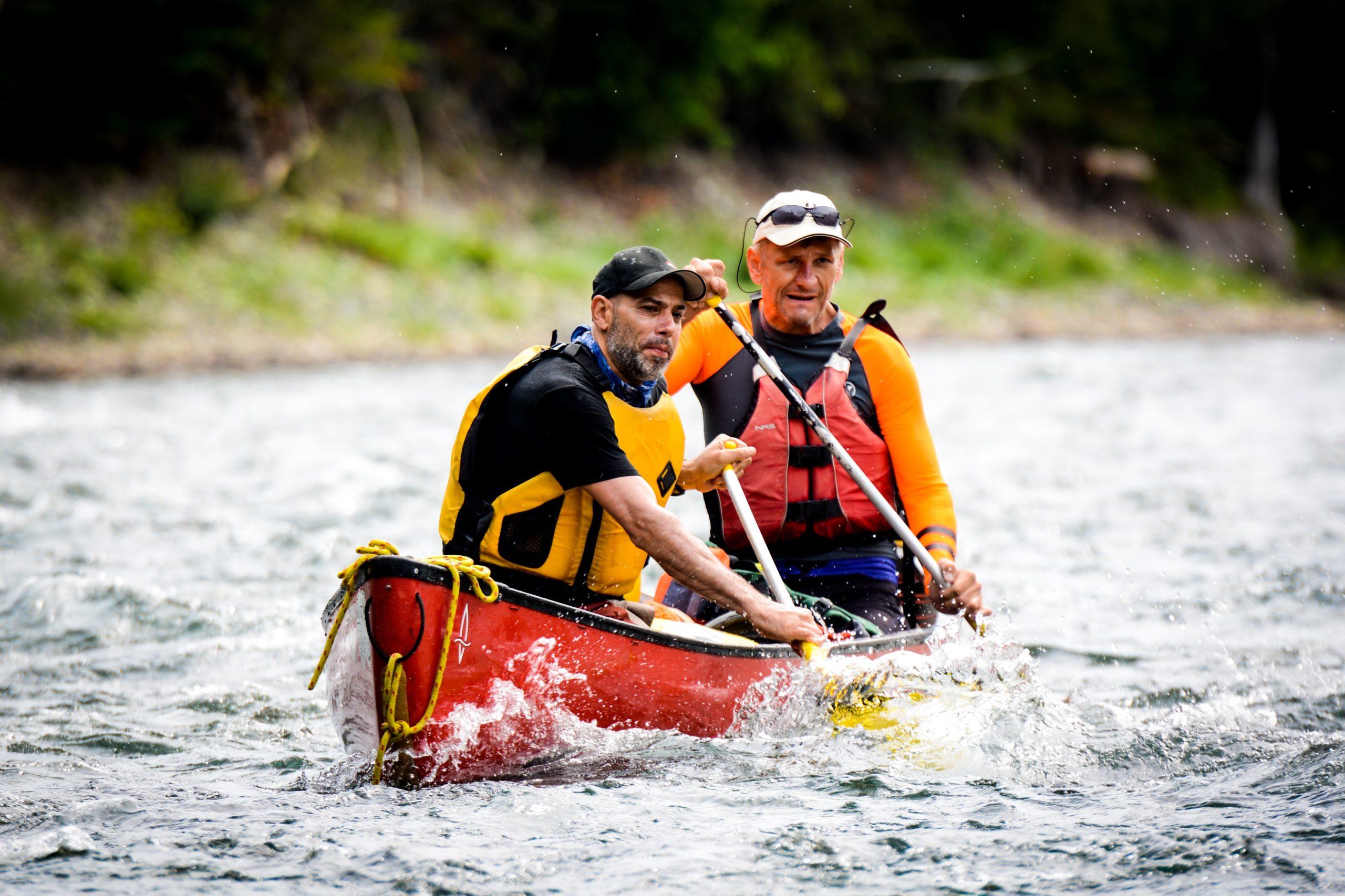 People canoe down river rapids.